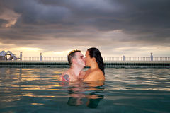 Kiss of loving couple in the swimming pool Stock Photography