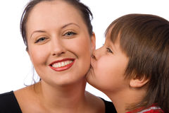Kiss me. Little boy kissing his mother on the cheek Royalty Free Stock Images