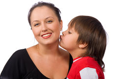 Kiss me. Little boy kissing his mother on the cheek Royalty Free Stock Image