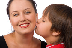 Kiss me. Little boy kissing his mother on the cheek Stock Images