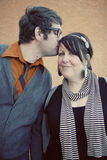 Kiss me. Close up of handsome stylish trendy man kissing a pretty girl wearing black and white scarf Stock Photos