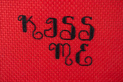 Kiss Me cross stitched on red Stock Photography