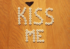 Kiss me note. Kiss me button note on wood background Royalty Free Stock Photography