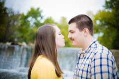 Kiss Me You Fool!. A happy young men and women by a waterfall on a pretty day Stock Photography