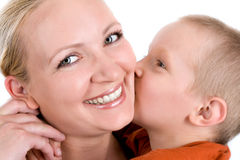 Kiss for mom. Little son kissing his mother on the cheek royalty free stock photo