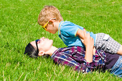 Kiss mother with son. Mother and son kissing lying on the grass Stock Photo
