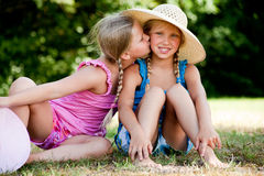 Kiss on my sisters cheek. Two little girls in fresh colors in the park Stock Photography