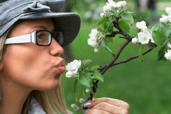 Kiss in the nature. Close-up portrait of girl in nature holding the apple tree branch with white flowers Royalty Free Stock Image