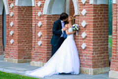Kiss near the ancient walls. Near the old brick walls are in full growth a kissing young couple newlyweds Royalty Free Stock Image