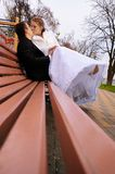 Kiss of newlyweds on a bench Royalty Free Stock Image