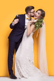Kiss of newlyweds. Standing on a yellow background Stock Images