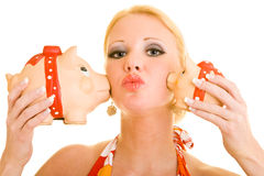 Kiss from piggy banks. Blonde woman gets kisses from two piggy banks on her cheeks Stock Photography