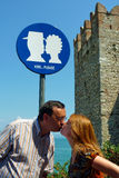 KISS...PLEASE. A couple obeying a fun sign seen by a castle in Italy (Lake Garda in Sirmione), requesting couples to kiss Royalty Free Stock Images