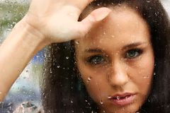 Kiss the rain. Young woman on the wet glass Stock Photo