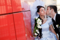 Kiss by the red wall Stock Photography