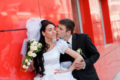 Kiss by the red wall royalty free stock photo