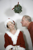 Kiss Rejected. Woman dressed in a red mrs claus, elf or pixie costume rejecting a kiss from a man under the mistletoe Stock Photos