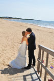 A Kiss by the Sea. A Young wedding couple kisses softly with standing on the sand by the beach and at the side there are some toys symbolizing that in a few Stock Image