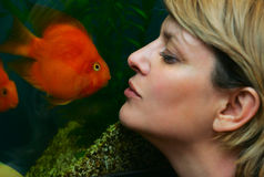 Kiss of a small fish. And the beautiful woman Royalty Free Stock Photography