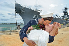 The Kiss Statue. USS Missouri on the background. Entitled Unconditional Surrender this statue by noted artist J. Seward Johnson, commemorates the famous The Kiss Stock Image