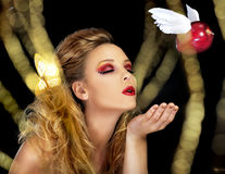 The Kiss of Temptation. A magical scene where a beautiful blonde model blows a kiss, represented by a red apple with wings, through a field of gold Stock Photography