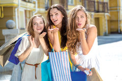 Kiss from three girlfriends. Three girls holding shopping bags a Royalty Free Stock Image