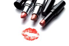 Kiss and three lipsticks. Three lipsticks and a kiss on a white background Stock Image
