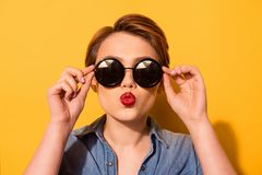 Kiss for you! Fashionable young cute girl in trendy sunglasses s. Ends a kiss against bright yellow background, she holds spectacles with her hands stock photos