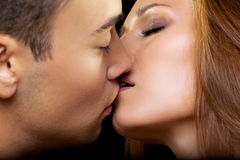 Kiss. Young couple of lovers kissing on black background Stock Images