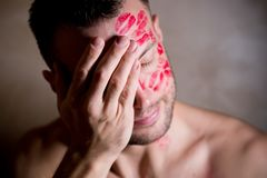 Kissed man with traces of lipstick bashfully covers his face with his palm