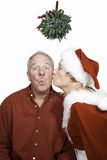 Kissed Under the Mistletoe. Man sitting under mistletoe being kissed by a women in a red mrs claus, elf or pixie suit Royalty Free Stock Photography
