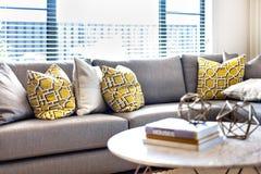 Kissen auf dem grauen Sofa neben einem Fenster und einem Sonnenlicht Stockbild