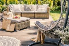 Kissen auf Rattancouch und -tabelle auf Patio mit hängendem Stuhl DU stockbild