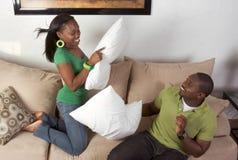 Kissen, das zwischen jungen schwarzen ethnischen Paaren kämpft Lizenzfreies Stockbild