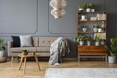 Kissen und Decke auf beige Couch im grauen Wohnzimmerinnenraum stockfotos
