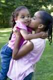 Kisses. Two Bi-racial sisters at the park.  Big sister holding and giving little sister a kiss Stock Images