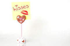 Kisses. Close up of a postit note saying kisses isolated on white Stock Photo