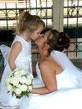 Kisses. A bride kissing her flower girl royalty free stock photography