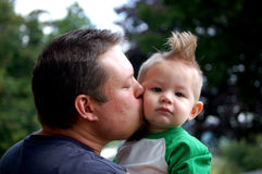Kisses from Daddy. Father giving his son a kiss on the cheek Royalty Free Stock Photos