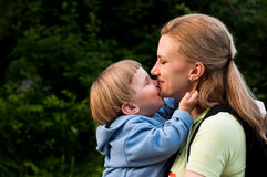 Kisses and hugs between mother and daughter Stock Photos