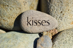 Kisses Message Carved on a Rock. A carved rock in the middle of a pile of stone rocks with the message kisses carved on it Stock Photography