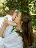 Kisses so Sweet. Mom and daughter are together in garden.  She has long brown hair and daughter has pink bow in her hair.  Mom is kissing baby on the cheek Stock Photos