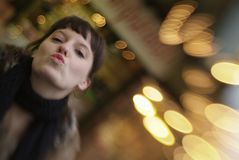 Kisses for you. A young woman is kissing in the air with blurry background stock photos