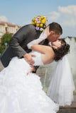 Kissin des Bräutigams und der Braut in ihrem Hochzeitstag Stockfotografie