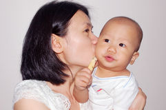 Kissing. Mother kissing her baby boy Royalty Free Stock Photos