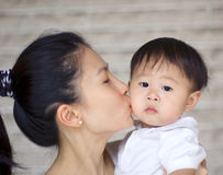 Kissing. Asian mother kissing her baby boy Stock Photography