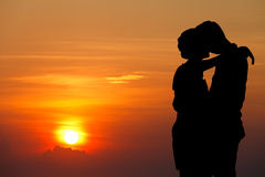 Kissing. Silhouette couple kissing over sunset background Stock Photography
