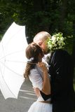 Kissing. Bride and groom kissing in the park stock photo