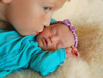 Kissing baby. Older brother kissing newborn baby sister Royalty Free Stock Image