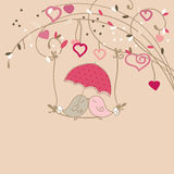 Kissing birds. Two lovely birds sitting on a branch swing and kissing under the umbrella Stock Images